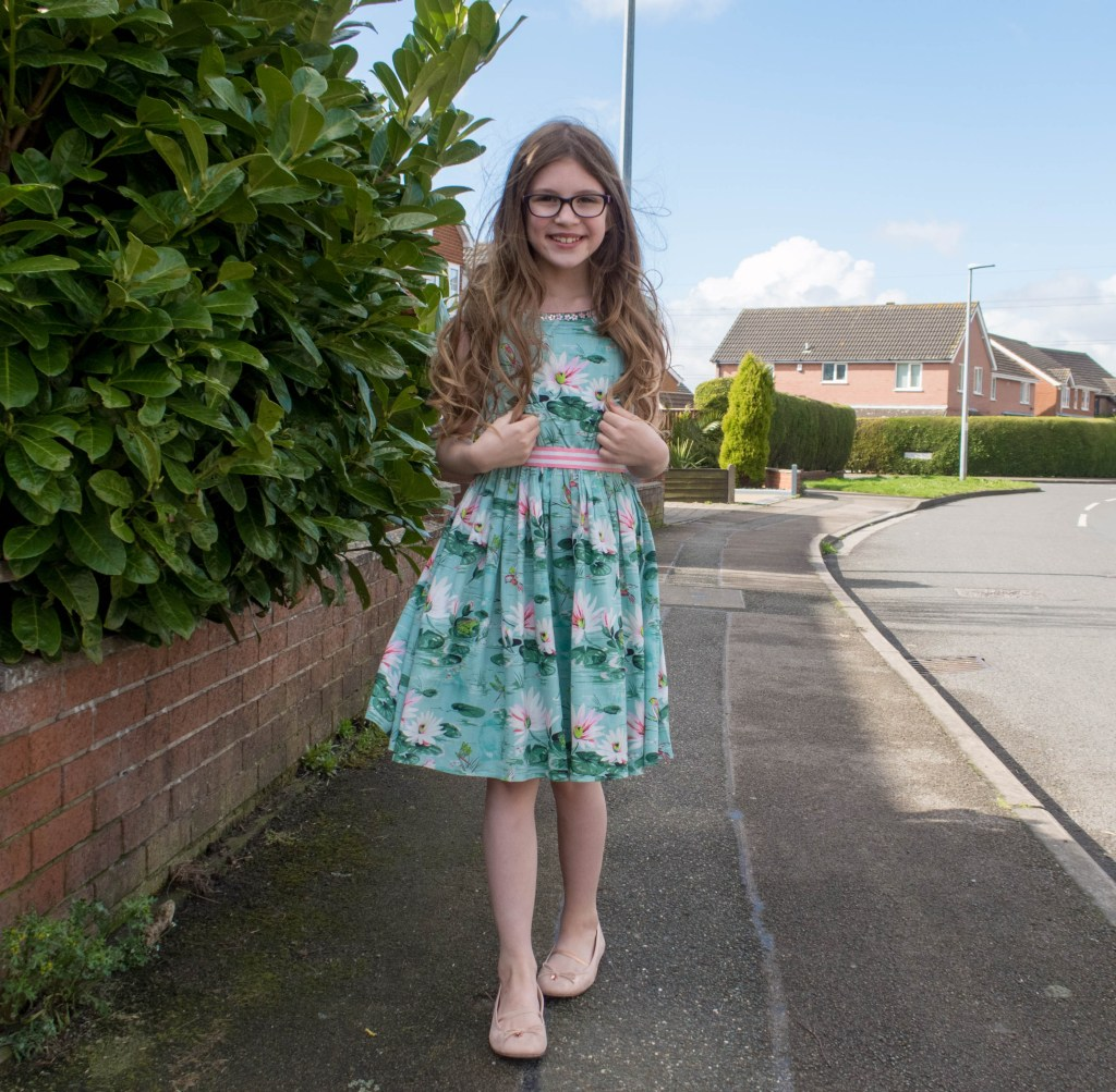 Emma wearing a Monsoons girls spring dresses in a blue/green lily printed paterm with a pink and whie candy striped fabric belt. Emma is tall and thin and have long light brown curly hair, black glasses and is smilying
