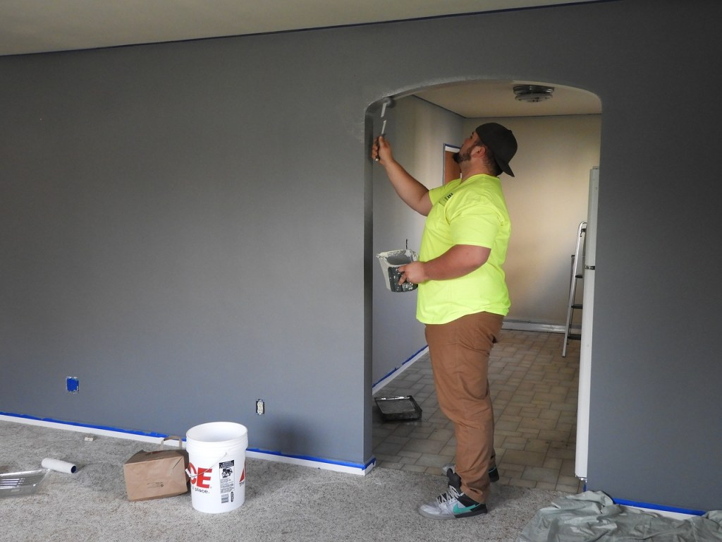 Man wearing a yellow short, painting a doorway in a grey room