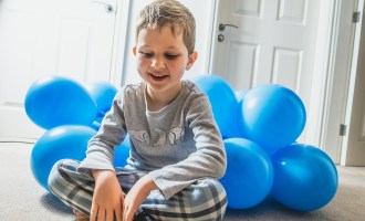 Greg smiling with balloons behind him