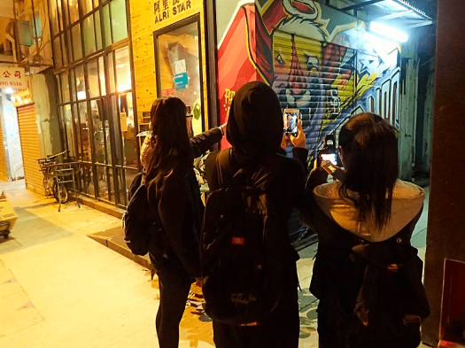 Image-of-university-students-photographing-wall-mural-in-Kowloon