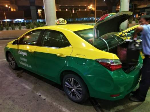 taxi-driver-loading-luggage-into-taxi-trunk