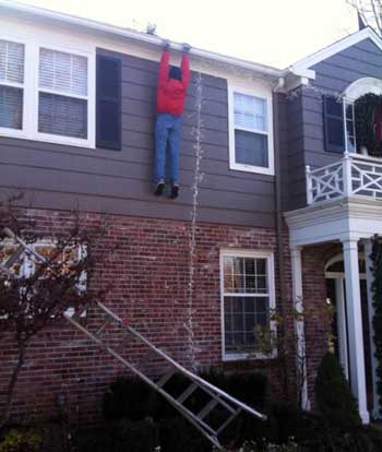 Guy holding onto roof after losing ladder
