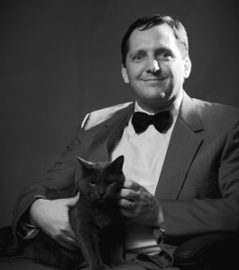 "This is a picture of me sitting with October, our ""blue"" cat. Its in black and white and I look sort of like a pasty white super-villain from a James Bond film."
