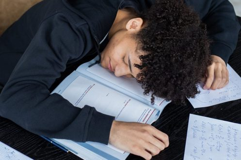 Man lying asleep on opened textbook and homework papers