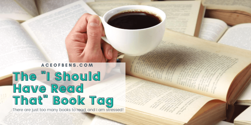 Photo of a hand sticking out of a pile of open books that is hold a cup of coffee. The title text over it says 'The I Should Have Read That Book Tag' and the subtitle under it says 'There are just too many books to read and I am stressed.'