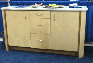 photo of custom-made blonde wood credenza with large end cabinet doors and three central drawers plus marble top