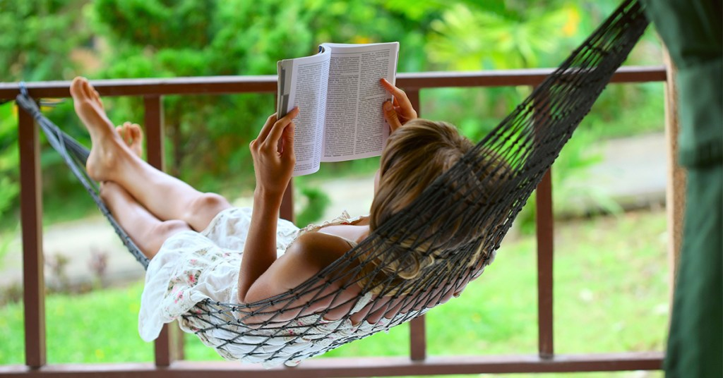 a woman reading in a hammock enjoy nature in a peaceful setting