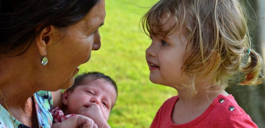 """First meeting"": Older woman with Asian features, holding infant, talks to young Caucasian girl"