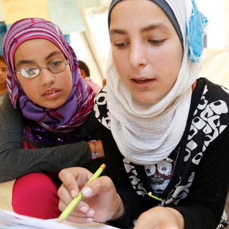 Alia and Basma* (right), both aged 12, tackle a maths question at a temporary school in northern Lebanon