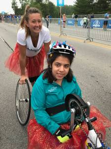 Guide Amanda Hachey behind Athlete Sara Solomon in handcycle at Geist Half Marathon