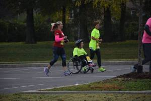 Wheelchair athlete being guided by runners running beside