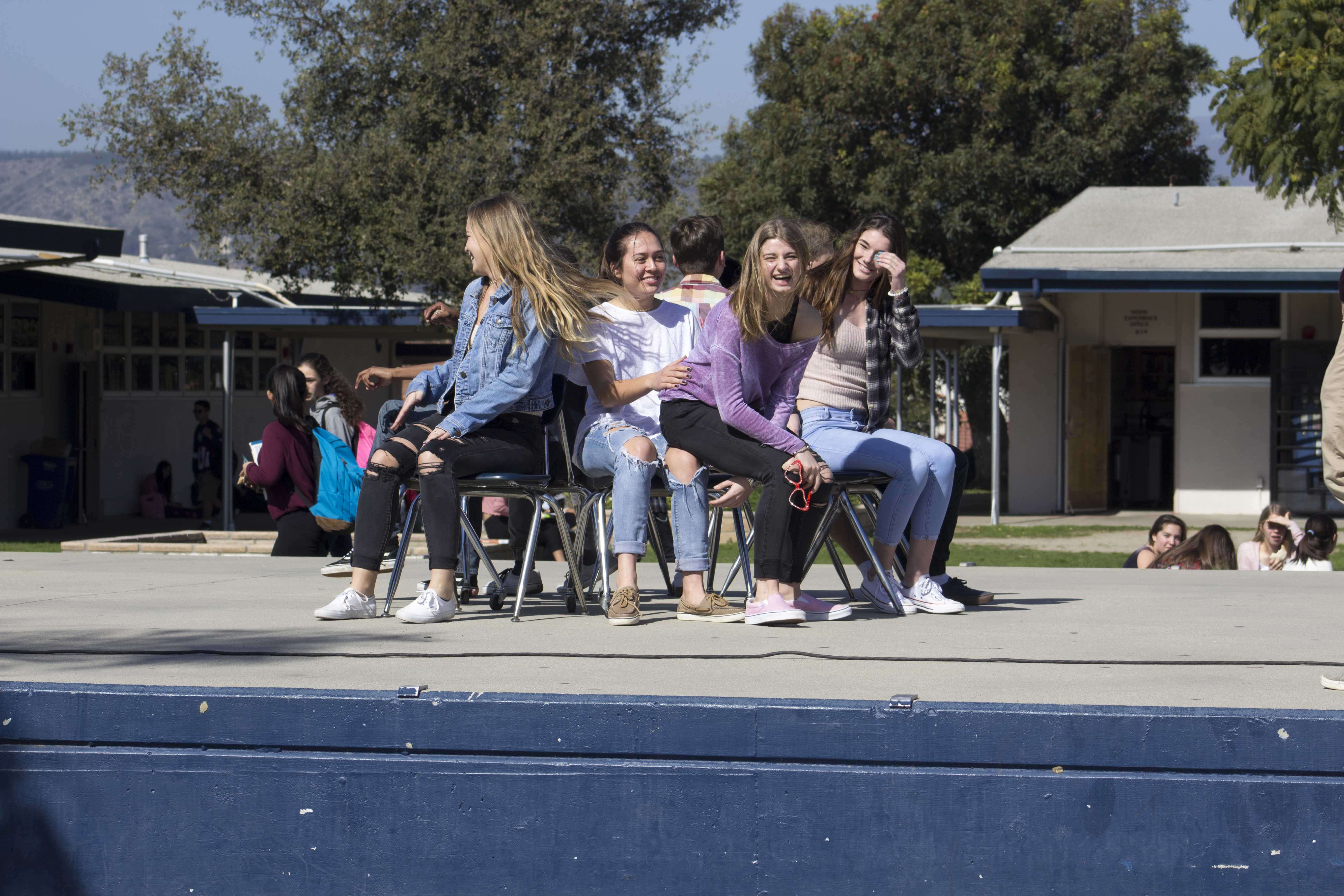 Melodie Truchi sitting on Karina Duffy (sophomores) while rushing for a spot during musical chairs.