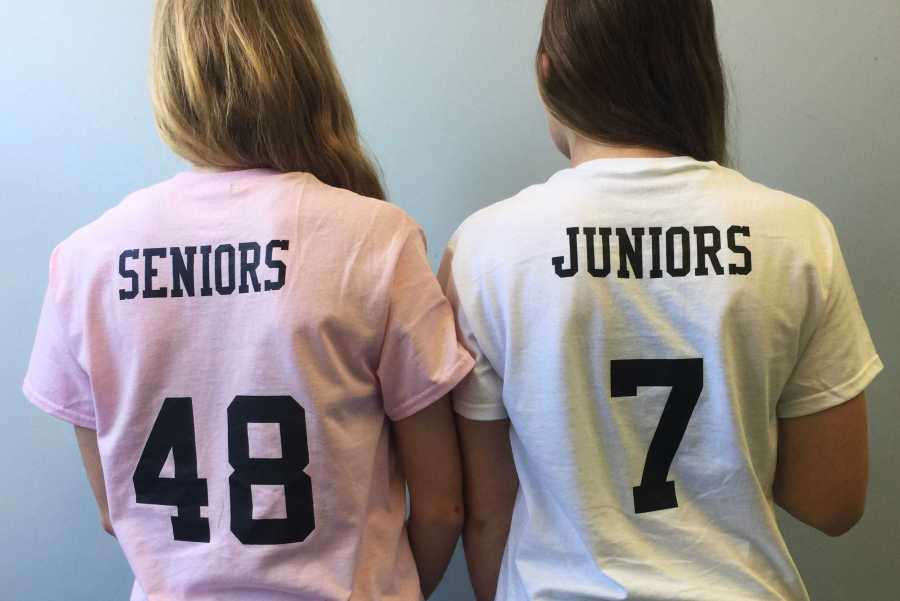 Juniors+and+seniors+stand+together+as+they+prepare+for+the+powderpuff+game.