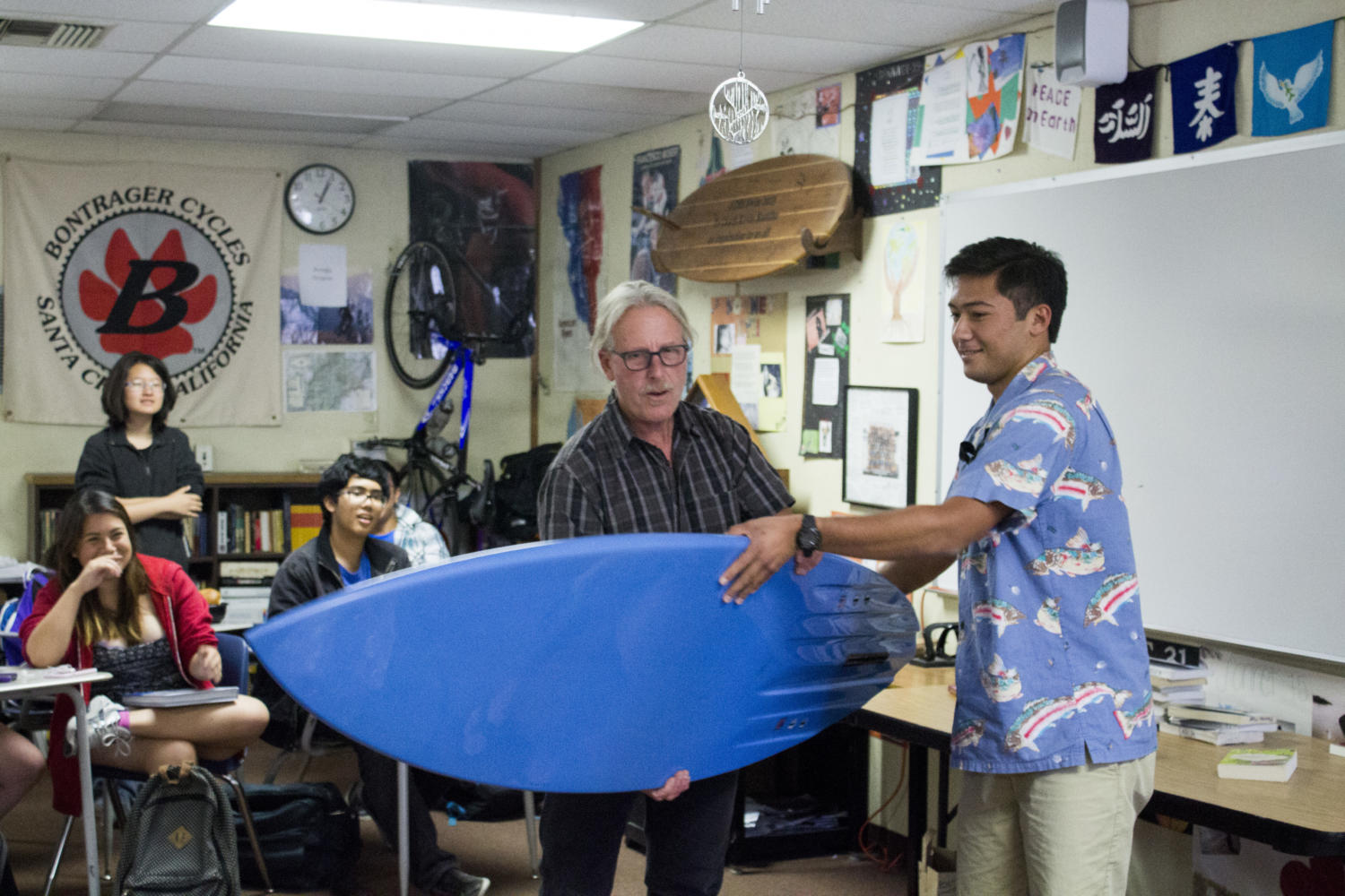 Senior Tyler Tsuji hands Mr. Kevin Buddhu his customized surfboard presented by his AP Literature classes as a goodbye gift before he leaves to Spain.