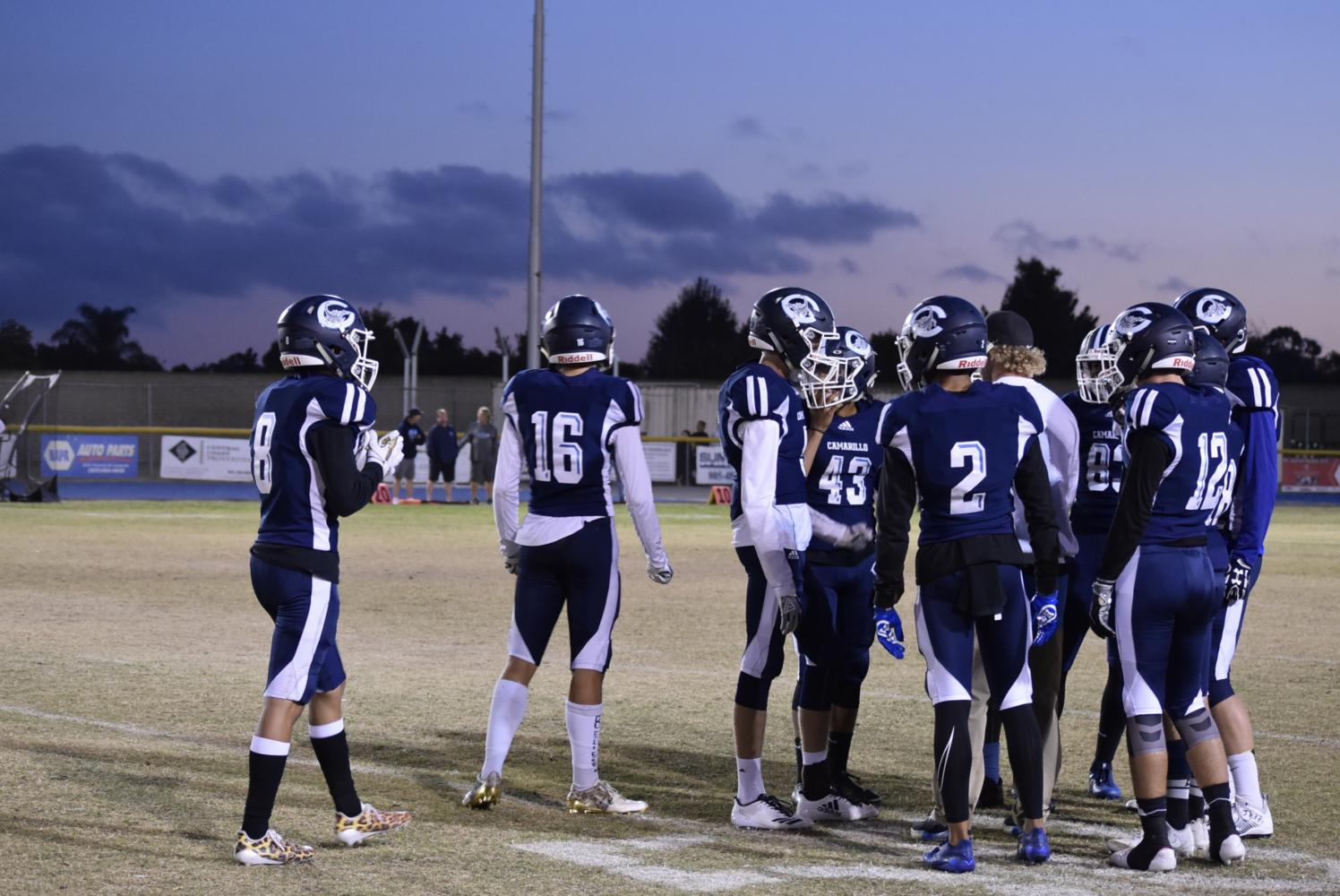 The football team huddles around their coach to prepare for the next play.