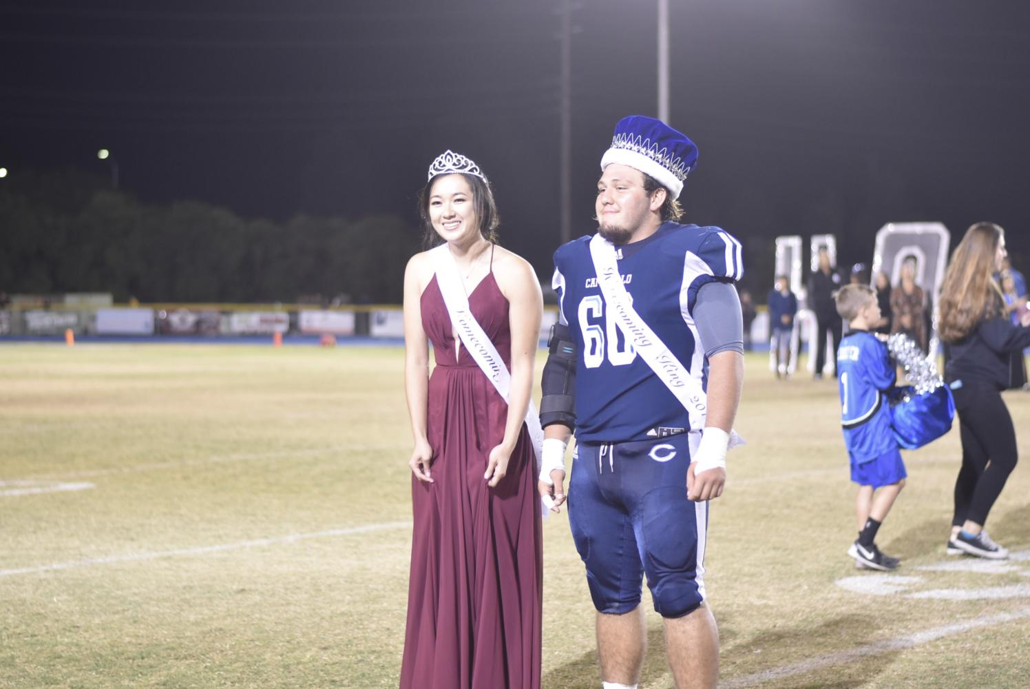 The Senior Homecoming Queen and King, Marissa Hiji and Damian Medina, stand before Cam High shortly after being crowned.
