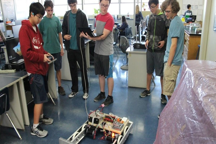 Robotics+team+gathers+around+their+robot+at+week+2+of+construction.