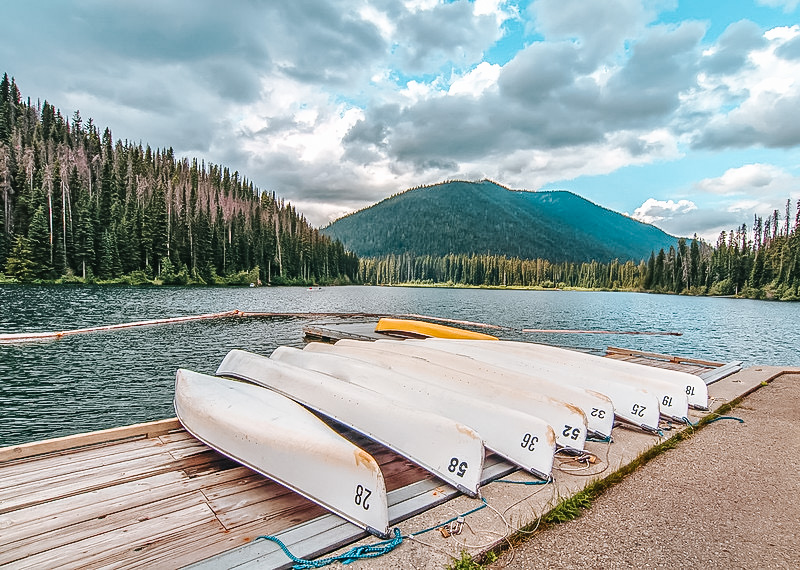 Photo of a lake on a windy day with trees and a small green mountain in the background. In the foreground is a wooden dock with upside down white canoes lined alongside each other. Manning Park is a 2-3 hour drive from Vancouver