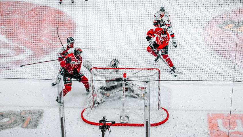 Photo of an ice rink with four hockey players, two wearing a red jersey and two wearing a white jersey, holding hockey sticks with a goalie standing in the goal.  A hockey game is one of the best Vancouver rainy day activities.
