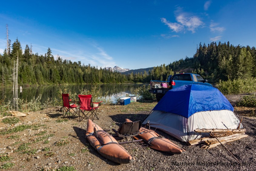 Photo of a lake in the mountains with blue skies. In the foreground is a camping set-up. A blue tent in the front of the photo, a pontonn fishing boat next to it, red champing chairs to the left and just right of that is a cooler and just behind the tent is a blue tuck