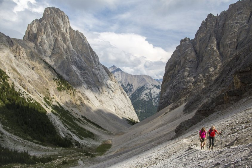 Photo showing two hikers on a rocky hiking trail with huge mountain peaks in the background.