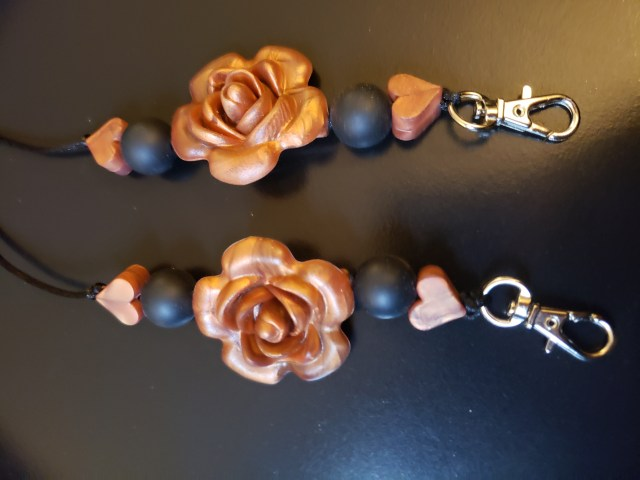 Mask lanyard with copper roses and hearts and black beads.