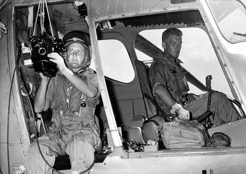 News cameraman Les Wasley with a Cemeflex 35mm Camera, ready for take-off from the aircraft carrier HMAS Melbourne while filming military exercises in the Philippines in 1961 - PHOTO Cou
