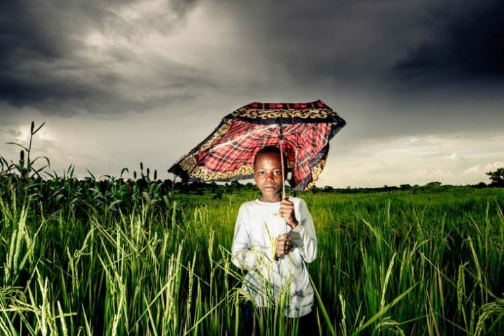 A portrait of Zephania, a 12 year old boy from Butaleja sheltering himself from drizzles as he keeps birds away from his family's rice field. Taken on 11.04.2015. Scaring birds away from farms is a daily routine for many young people who do not go to school.