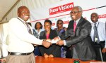 Senior editor Bukedde receives a copy of the editorial policy from Vision Group CEO Robert kabushenga (R) early this month. Photo by Maria Wamama/Vision Group