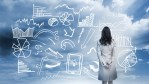 Businesswoman standing looking at data flowchart in cloudy landscape