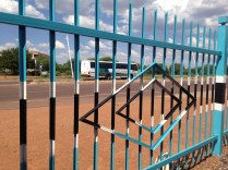 The Botswana flag is painted EVERYWHERE in Botswana. Here, you can see it's colors on the gate, with our bus in the background