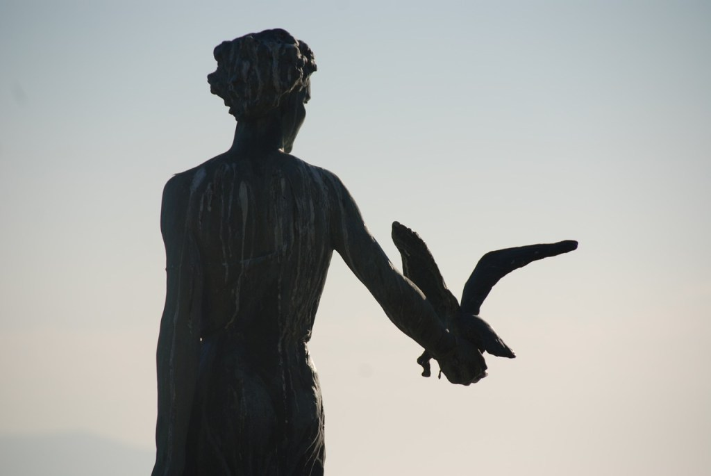 Female statue covered in poop, with a seagull in her hand