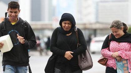 Foto de pessoas andando agasalhadas