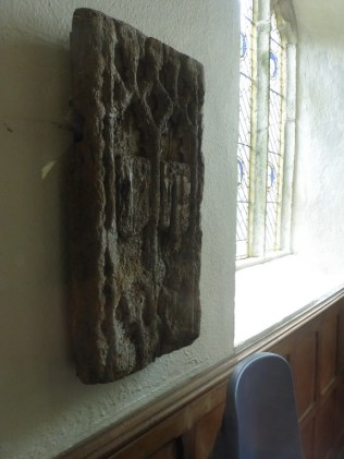 Possibly a former bench end, displayed just inside the porch