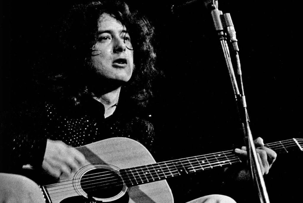 black and white photo of Jimmy Page seated playing his acoustic guitar