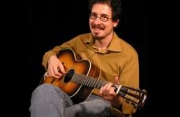 photograph of david hamburger smiling while playing an acoustic guitar