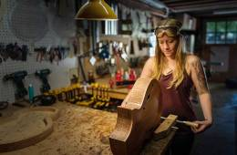 Luthier Maegen Wells in her workshop with an archtop guitar