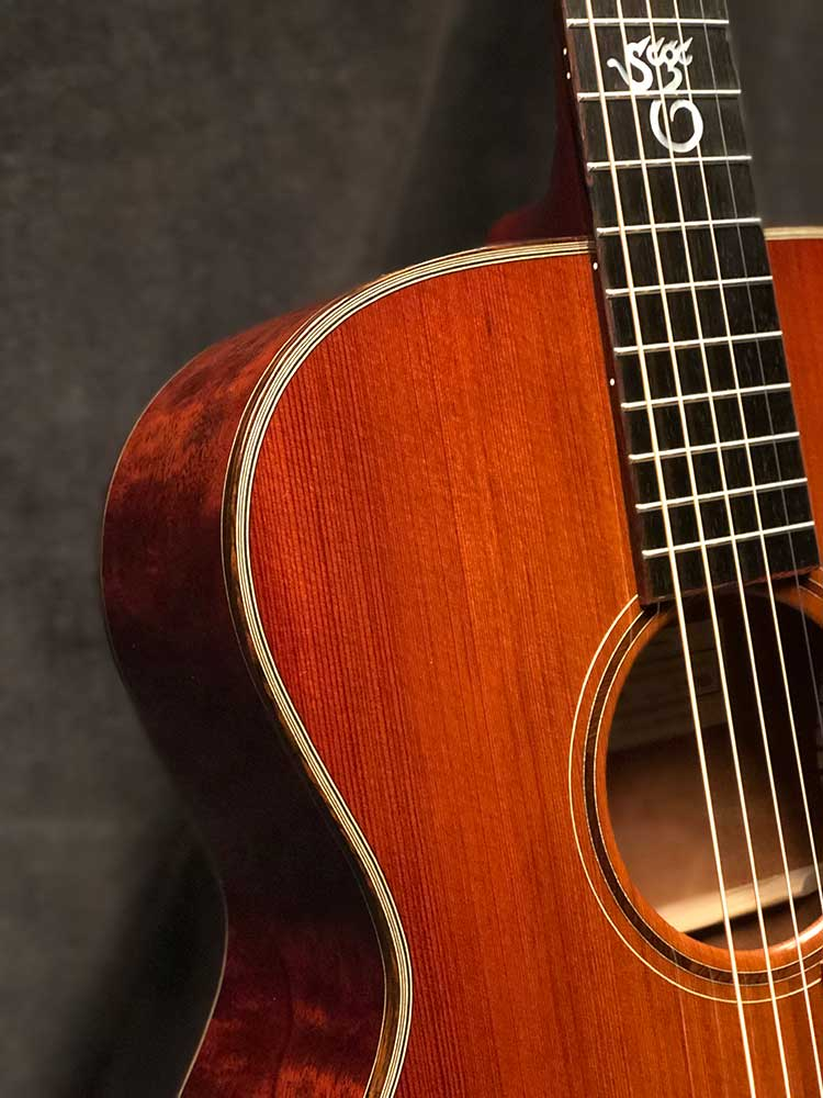 Closeup of binding, strings, and soundhole of a 2021 Santa Cruz OM Custom acoustic guitar made from Tunnel 13 Redwood