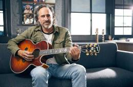 """James """"JC"""" Curleigh, CEO of Gibson Guitars, seated holding an acoustic guitar"""