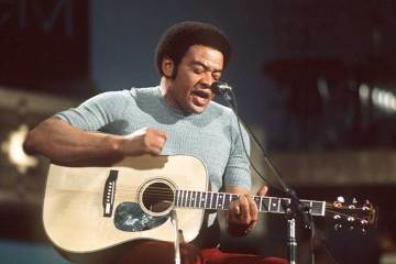 Bill Withers playing acoustic guitar and singing
