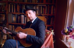 guitarist john doyle sitting in a chair in home library with guitar