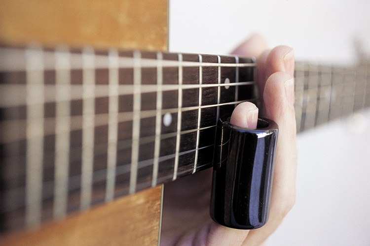guitar being played with slide on pinky viewed from the soundhole up the neck