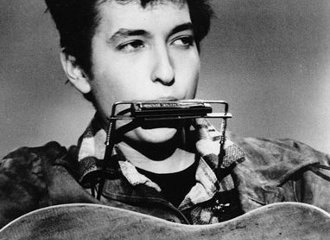 Young Bob Dylan playing harmonica with a neck rack while holding acoustic guitar