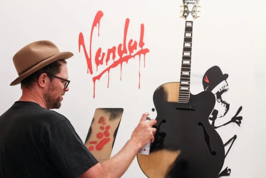 Nick Walker spray-painting his work.