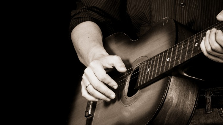 black and white photograph showing close up of hands playing blues guitar