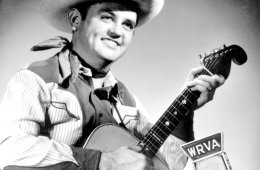 Guitarist Merle Travis, dressed in western clothes, picks an acoustic guitar