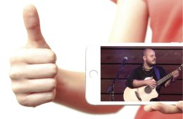phone showing musician playing acoustic guitar in front of a woman giving a thumbs up