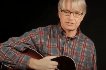 photograph of scott nygaard in a plaid shirt demonstrating a chord position on acoustic guitar