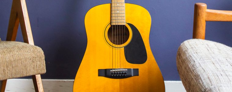 acoustic guitar on a stand in front of a blue backdrop