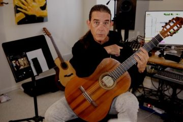 guitarist michael chapdelaine seated in his home studio holding a nylon-string guitar